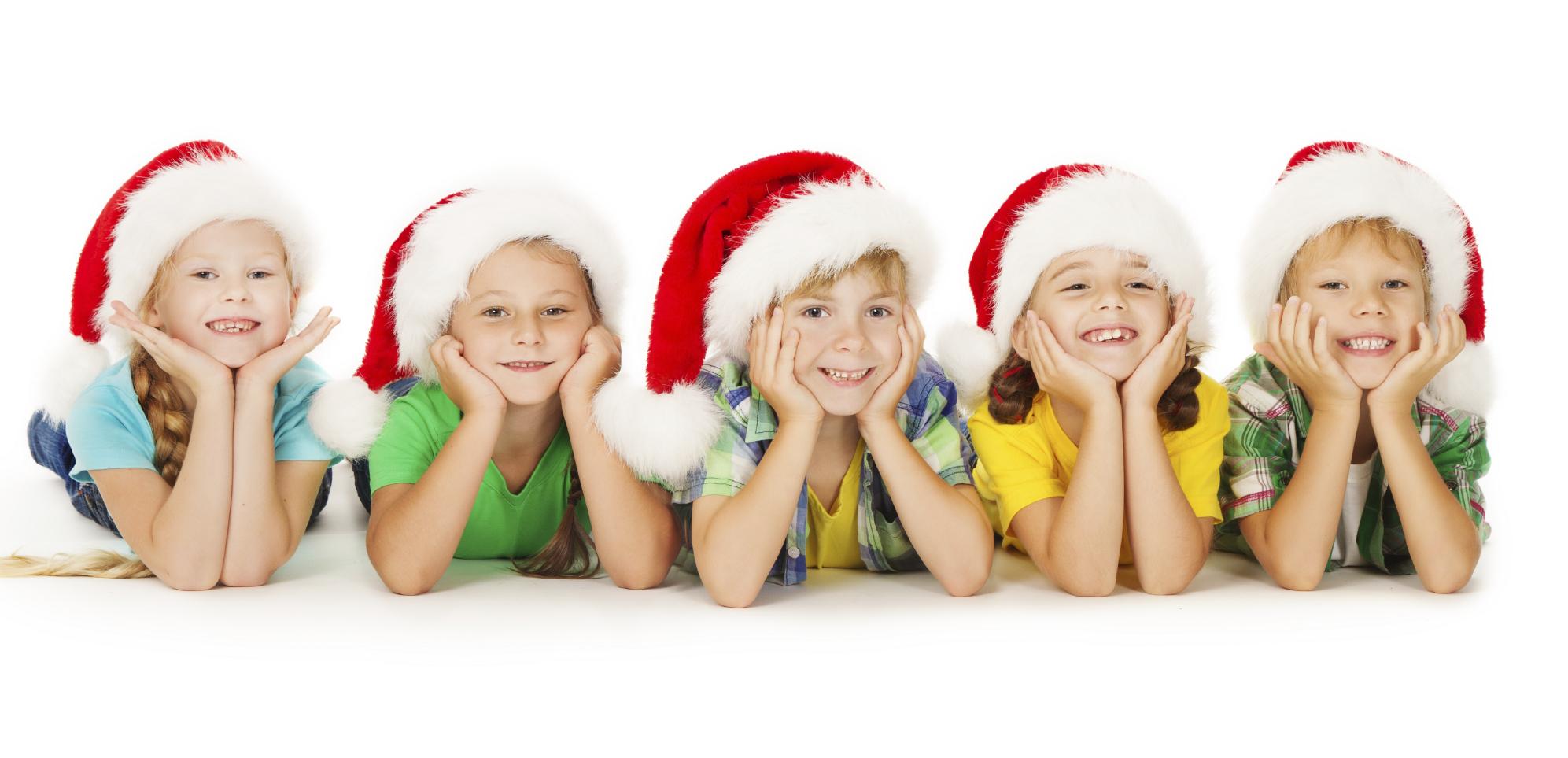 group of happy christmas kids in santa hat lying down white background cokesbury church - Kids Christmas